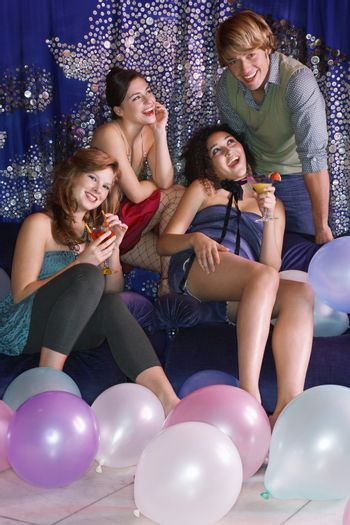 Young man leaning over sofa enjoying attention of women at social event