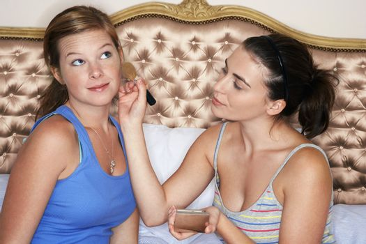 Teenage girl sitting on bed and applying blush to friend's face