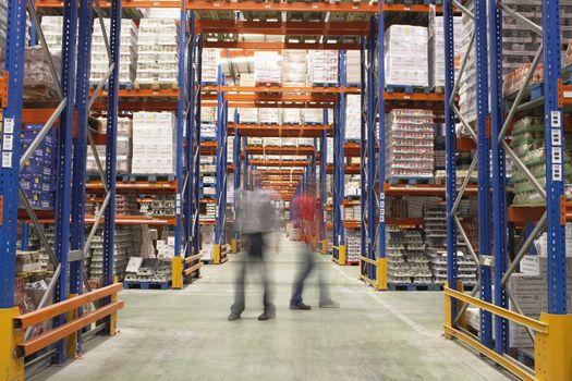 Blurred men walking in the warehouse