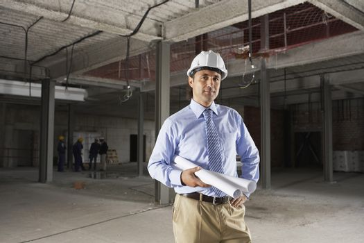 Portrait of a male site manager with blueprint at site