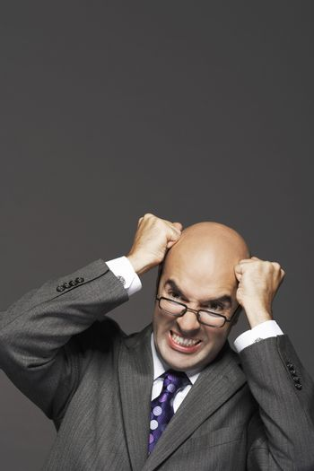 Bald businessman with fists pounding bald head against gray background