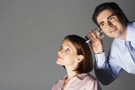 Businessman listening through glass to woman's head against gray background