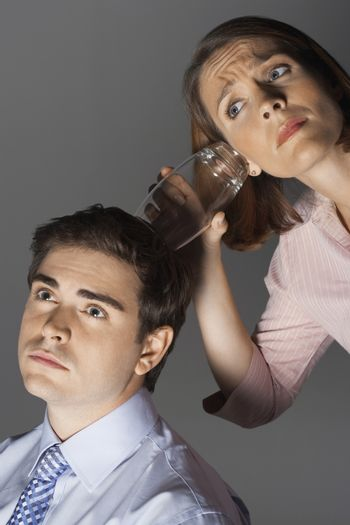 Closeup of a businesswoman listening through glass to man's head against gray background
