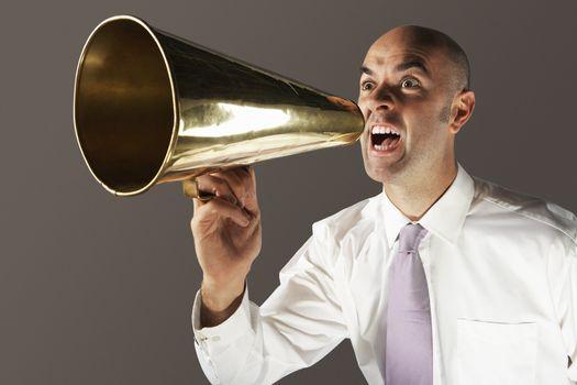 Bald businessman shouting through megaphone against gray background