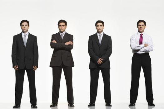 Full length portrait of businessmen standing side by side against white background