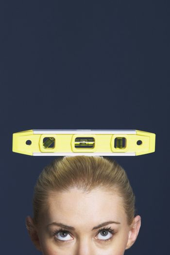 Extreme closeup of a businesswoman balancing spirit level on head against blue background