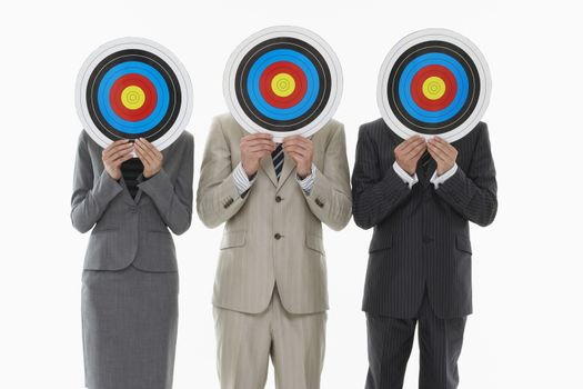 Three businesspeople holding targets in front of faces against white background