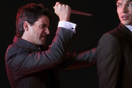 Businessman stabbing another man in back against black background
