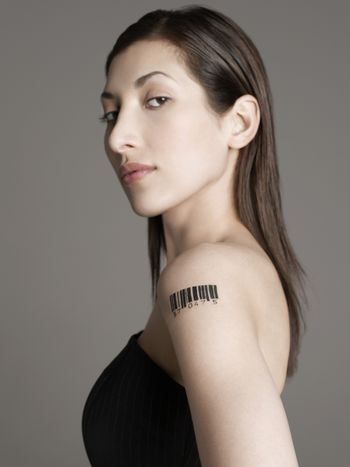 Portrait of a young woman with barcode tattoo on her arm against gray background