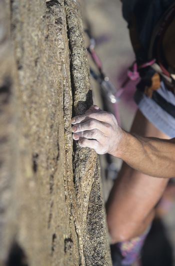 Cropped image of rock climber holding on to cliff