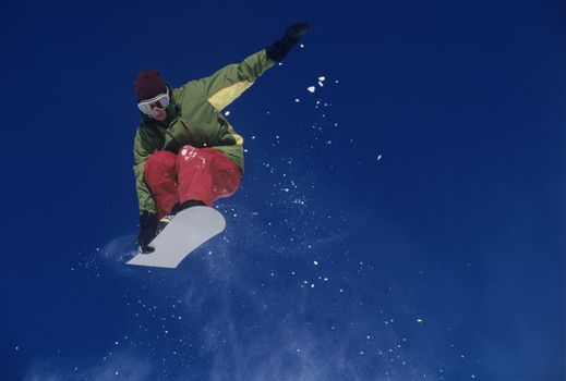 Snowboarder jumping holding snowboard