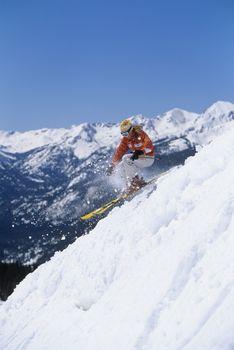Skier skiing down ski slope side view