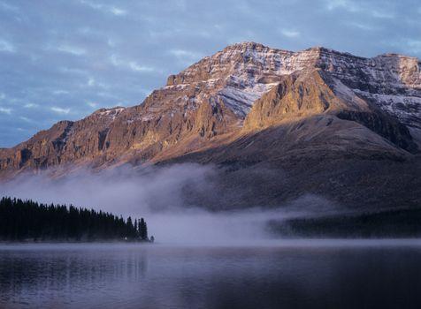 Rocky mountain fog over lake sunset