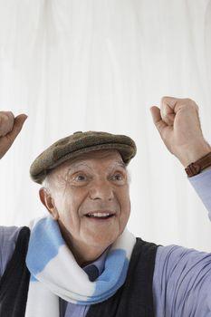 Senior man in football scarf celebrating in studio head and shoulders