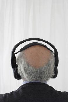 Senior man wearing head phones in studio head and shoulders back view