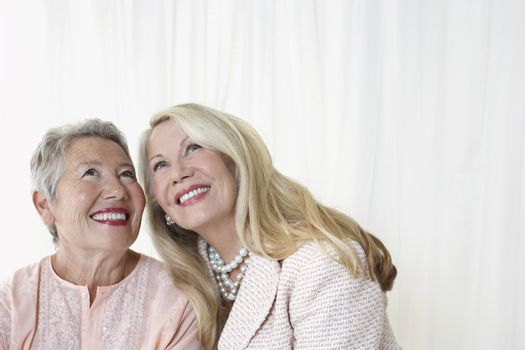 Two elegant senior woman in studio looking up head and shoulders