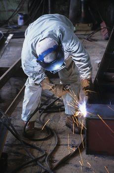 Welder bending down welding at Work