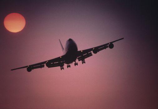 Plane Flying below setting sun at Sunset