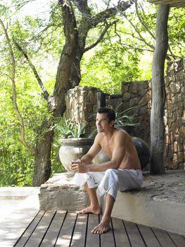 Young shirtless man on terrace enjoying the view