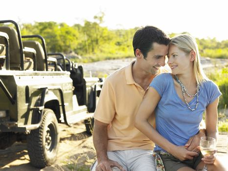 Loving young couple with wineglass with jeep in the background