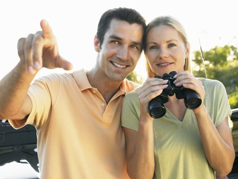 Happy man pointing while woman holding binoculars