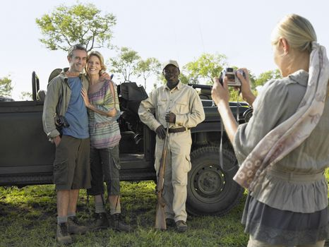 Couple and safari guide posing by jeep while young woman taking photograph