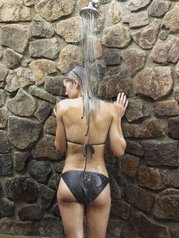 Rear view of a young woman in black bikini having shower against stonewall