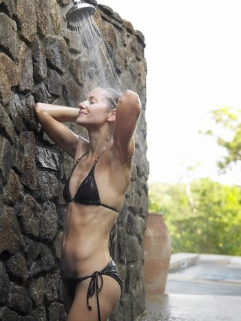 Side view of a young woman in black bikini having shower against stonewall