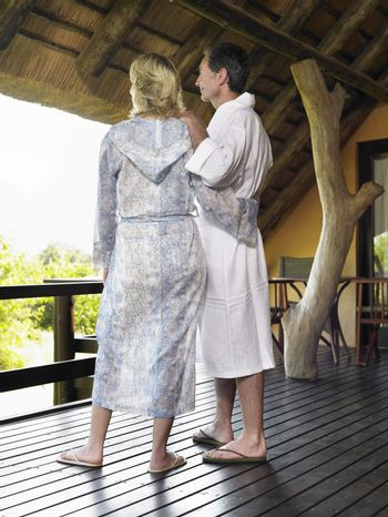 Rear view of an adult couple in bathrobes looking at view