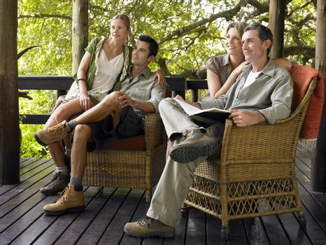 Two couples sitting in wicker chairs on terrace