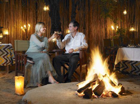 Man and woman toasting at outdoor nightclub near bonfire