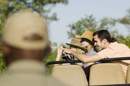 Tourists on safari pointing at view with blurred guide in foreground