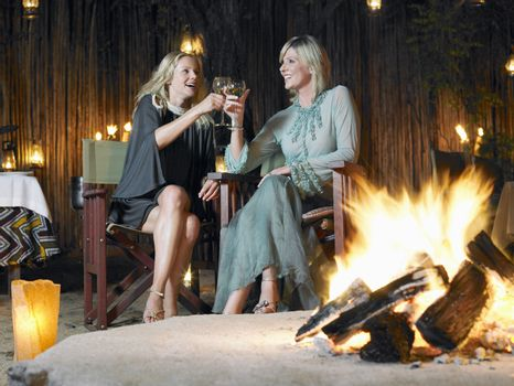 Two women sitting by bonfire at outdoor nightclub toasting