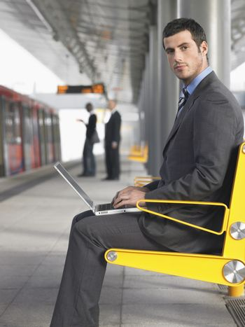 Businessman Using Laptop At Train Station