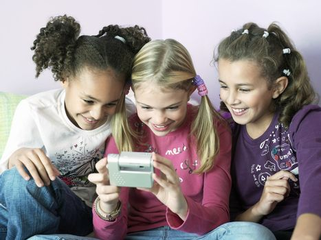 Young girls sitting side by side and playing with electrical gadget