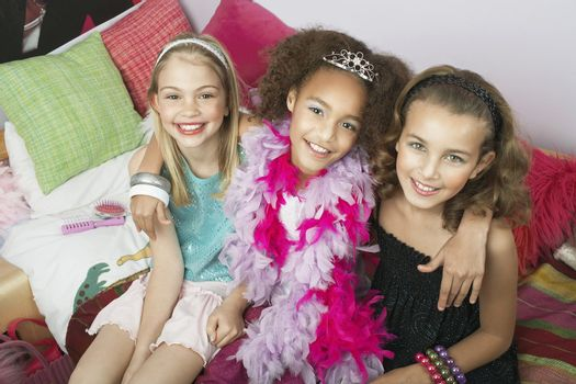 Portrait of three multiethnic girls sitting with arms around on trendy sofa at a slumber party