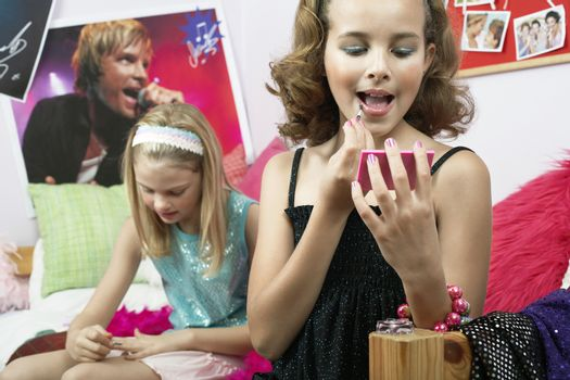 Fashionable young girls applying makeup in trendy bedroom