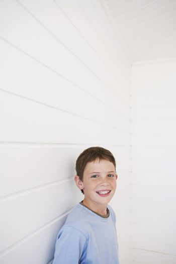 Portrait of happy young boy standing against weather boarded wall
