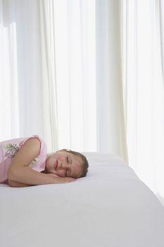 Girl sleeping on bed half length
