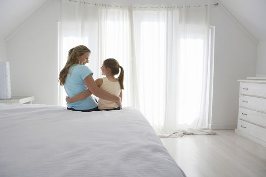 Happy mother and daughter sitting with arm around on bed