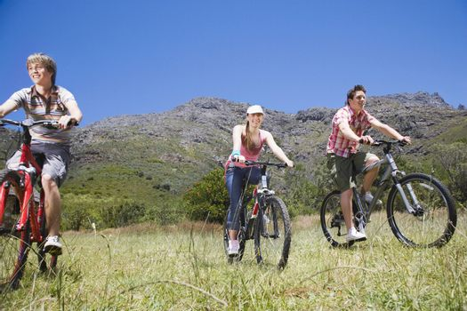 Teenage boys and girl biking with mountain in background