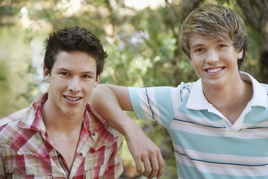 Portrait of two teenage boys smiling in forest