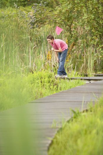 Young boy with butterfly net looking for wildlife in marsh