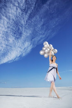 Woman holding balloons on beach