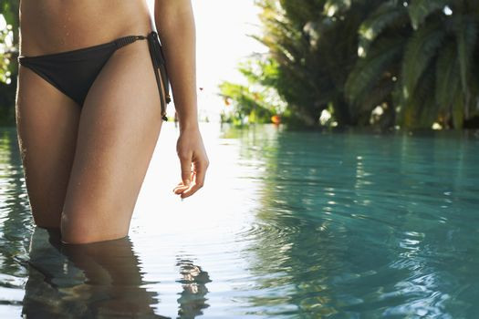 Midsection of sexy young woman wearing bikini bottom in outdoor pool