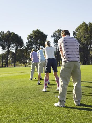 Golfers Standing In Row Teeing Off