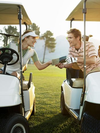 Young golfers sitting in golf carts holding score card on course
