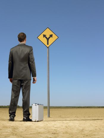 Rear view of businessman looking at road sign on desert