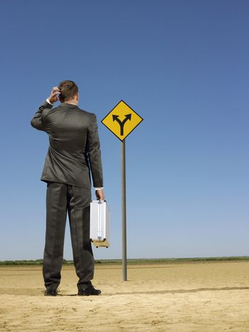 Rear view of confused businessman looking at road sign on desert