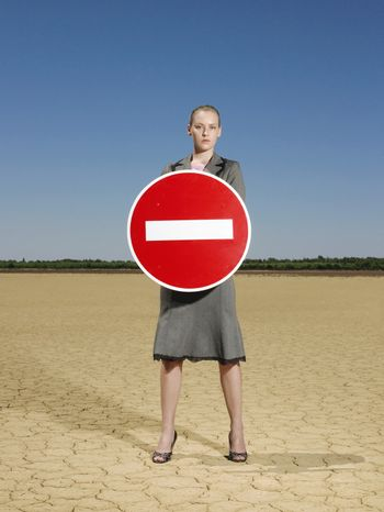 Full length portrait of young businesswoman holding 'No Entry' sign in barren landscape